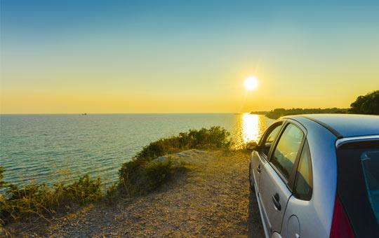 Photo of car overlooking lake and sunset
